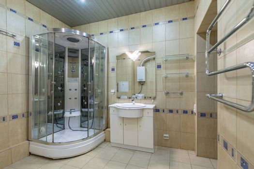 Small beige tile bathroom with Shower cabin and sink