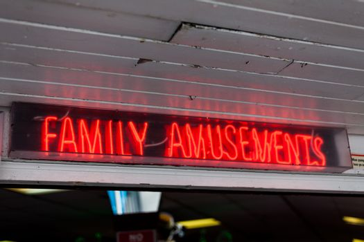 Family amusements sign on the street. Leisure concept with neon lights sign. Amusement park advertisement neon light. Advertisement with neon lights on the street.