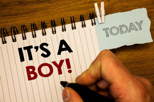 Text sign showing It S A Boy Motivational Call. Conceptual photo Male baby is coming Gender reveal CelebrationMan creating for today on notebook Hand hold holding pen Wooden background