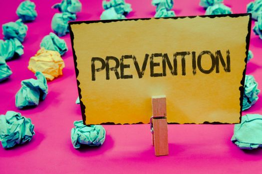 Conceptual hand writing showing Prevention. Business photo showcasing Stopping something from happening Healthcare ProtectionClothespin hold holding Yellow paper ideas crumpled papers pink background