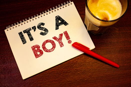 Words writing texts It S A Boy Motivational Call. Business concept for Male baby is coming Gender reveal CelebrationNotebook page black red letters pen ideas messages wooden table glass drink