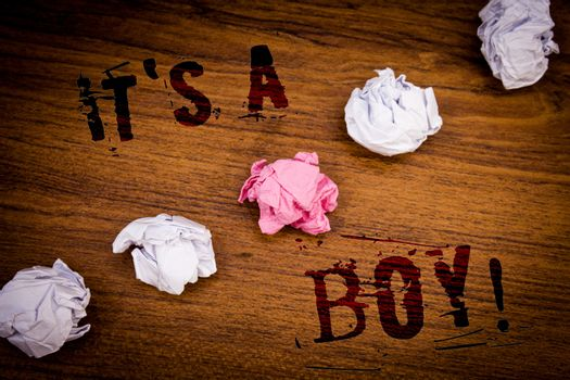 Handwriting texts It S A Boy Motivational Call. Concept meaning Male baby is coming Gender reveal CelebrationIdeas words wooden background black letters several tries crumpled papers