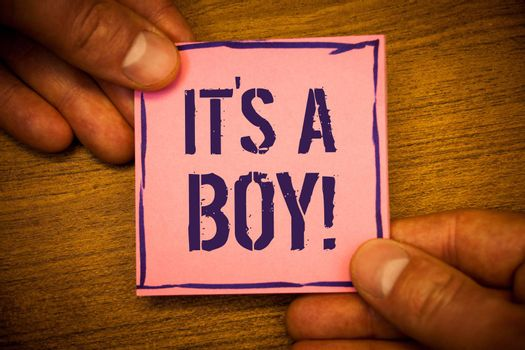 Conceptual hand writing showing It S A Boy Motivational Call. Business photo texts Male baby is coming Gender reveal CelebrationMan hold holding pink note ideas black letters wooden background