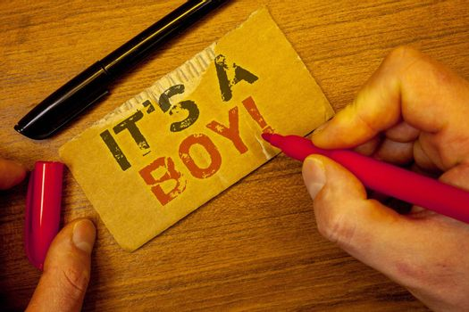 Writing note showing  It S A Boy Motivational Call. Business photo showcasing Male baby is coming Gender reveal CelebrationMan creating on yellow paper Hand holding red black pens wooden table