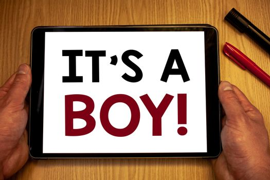 Text sign showing It S A Boy Motivational Call. Conceptual photo Male baby is coming Gender reveal CelebrationMan hold holding table with ideas words white screen black red pens wooden