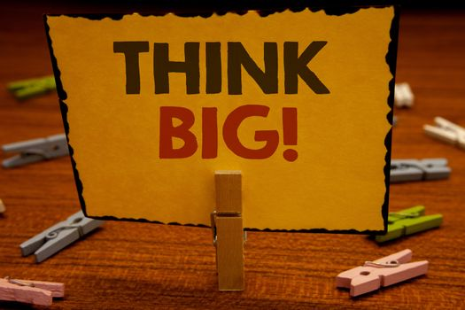 Words writing texts Think Big Motivational Call. Business concept for Have great ideas Dream of something amazingClothespin hold holding Yellow paper ideas clothespins wooden background