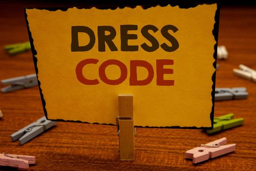 Words writing texts Dress Code. Business concept for Rules of what you can wear and not to school or an eventClothespin hold holding Yellow paper ideas clothespins wooden background