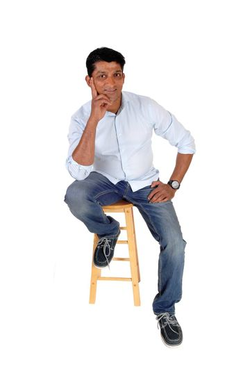 A smiling middle age man sitting on a chair in jeans and a blue shirt with one hand on his chin, isolated for white background