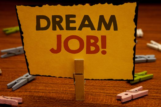 Words writing texts Dream Job Motivational Call. Business concept for To work in what you like Fulfilling activitiesClothespin hold holding Yellow paper ideas clothespins wooden background