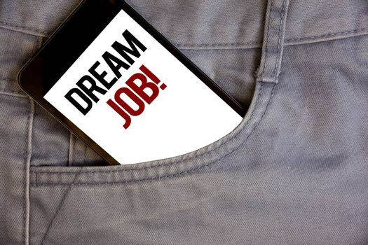 Writing note showing  Dream Job Motivational Call. Business photo showcasing To work in what you like Fulfilling activitiesConcept on cell phone on jean pocket white screen black and red letters