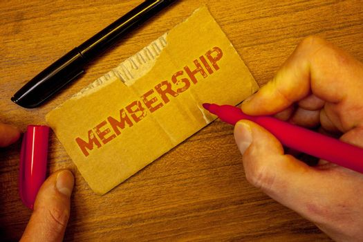 Writing note showing  Membership. Business photo showcasing Being member Part of a group or team Join an organizationMan creating on yellow paper Hand holding red black pens wooden table
