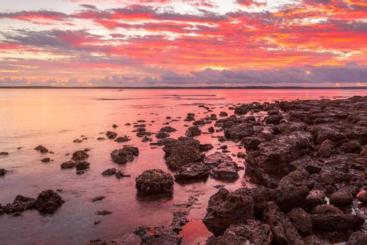 Rich red sunrise from the rockshelf at a small coastal township called Callala Bay a tranquil setting and suitable mooring for boats and yachts too.
