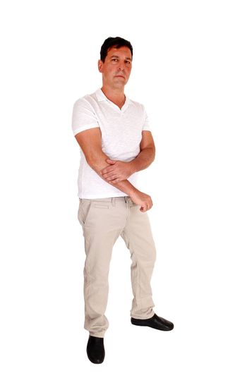A tall handsome middle age man standing in beige slacks and white t-shirt looking serious, isolated for white background