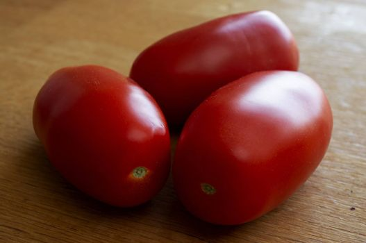 Three red tomatoes on wood table in sunlight.