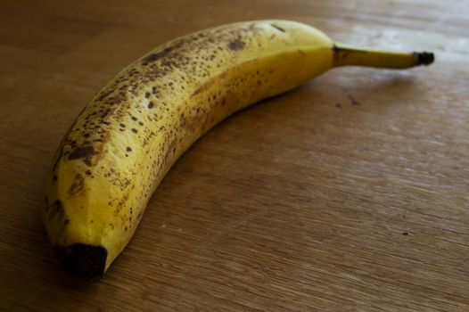 Brown spotted yellow banana on a table of wood.
