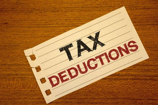 Writing note showing  Tax Deductions. Business photo showcasing Reduction on taxes Investment Savings Money Returns Text two word white paper note wood desk quick sketch school work pen
