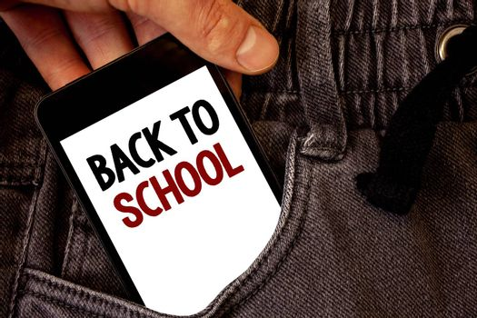 Text sign showing Back To School. Conceptual photo Return to class first day of studies Classroom Arriving Text two words on white screen black Phone Hand holding grey jeans pocket