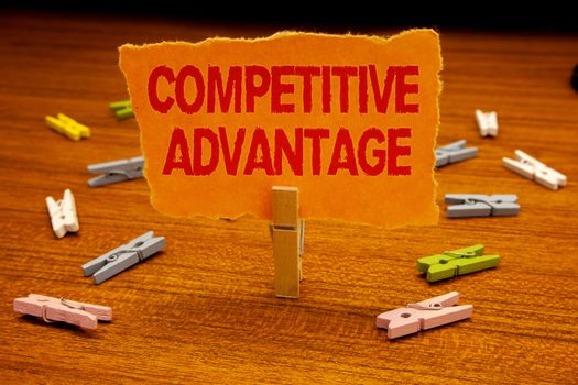 Writing note showing  Competitive Advantage. Business photo showcasing owning quality that will assure you leading in field Paperclip holding orange page show red text woody floor with clip