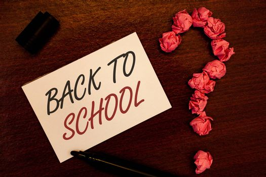 Text sign showing Back To School. Conceptual photo Return to class first day of studies Classroom Arriving Text white paper note black marker open cap pink crumbled paper question