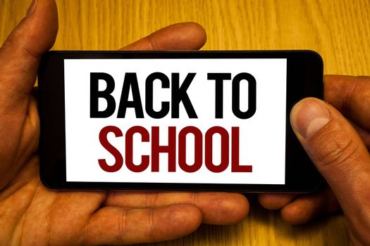 Text sign showing Back To School. Conceptual photo Return to class first day of studies Classroom Arriving Two hands holding black phone screen words written home button press