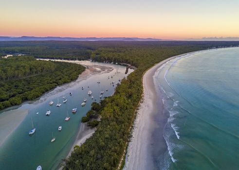 Scenic coastal landscape beautiful beach and inlet with moored yachts and boats.  Morning sky at dawn with soft light.  Australia