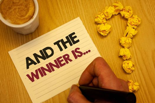 Conceptual hand writing showing And The Winner Is . Business photo showcasing Announcing as first place in competition or race Wooden desktop hand hold marker page coffee question mark