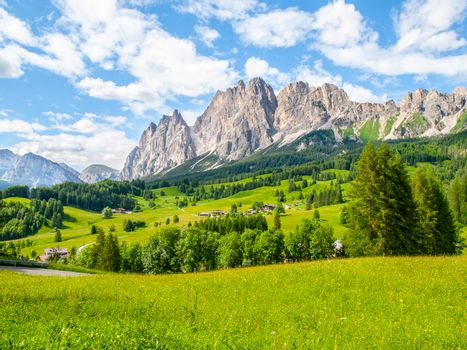 Rocky ridge of Pomagagnon Mountain above Cortina d'Ampezzo with green meadows and blue sky with white summer clouds, Dolomites,, Italy
