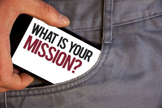 Word writing text What Is You Mission Question. Business concept for asking someone about his plans and to-do list Personage hand pushing mobile phone into back pocket fascinating way