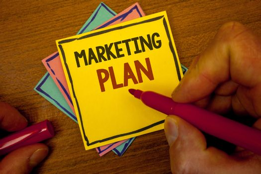 Conceptual hand writing showing Marketing Plan. Business photo text Business Advertising Strategies Market Successful Ideas Text colorful paper notes hand red marker open cap desk letter