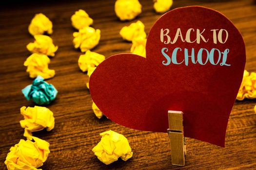 Text sign showing Back To School. Conceptual photo Return to class first day of studies Classroom Arriving Text red heart wood clip desk crumbled paper notes yellow blue love message