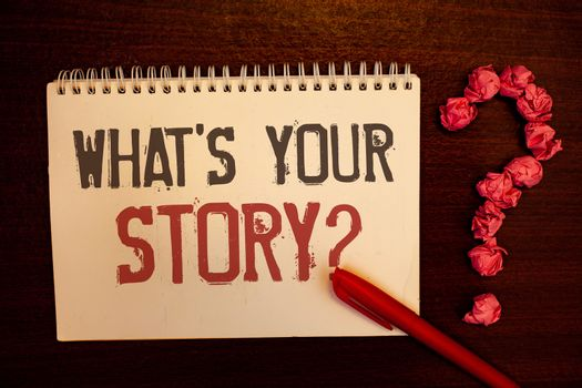Handwriting text What'S Your Story Question. Concept meaning Connect Communicate Connectivity Connection Reddish paper balls structures question mark red pen notebook browny desk