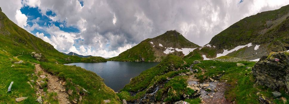panorama of Capra lake, Romania. gorgeous landscape of Fagarasan mountains on a cloudy summer day