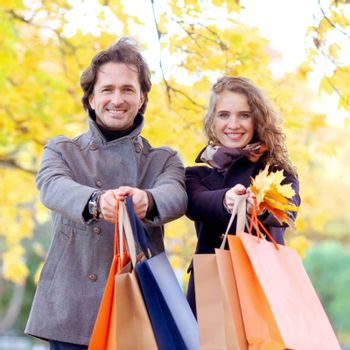 Cheerful couple with shopping bags in autumn park