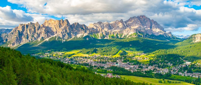 Panorama of Cortina d'Ampezzo with green meadows and alpine peaks on the background. Dolomites, Italy.