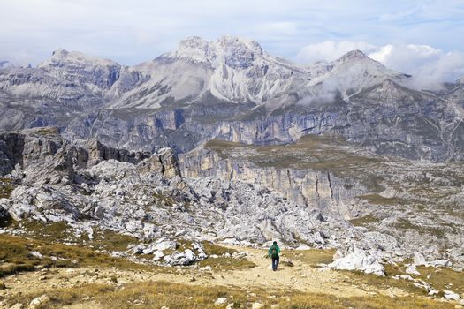 Hiker walking on a path in Dolomites, Italy