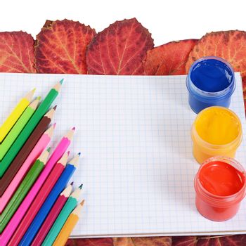Colored pencils with notebook and autumn leaves