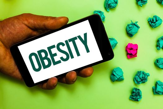 Conceptual hand writing showing Obesity. Business photo text Medical condition Excess of body fat accumulated Health problem Text message smart screen mobile handset crumpled small balls