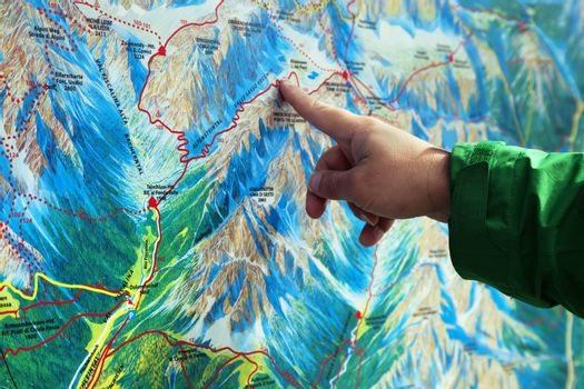 Finger pointing on a trekking map of an area in Dolomites, Northern Italy