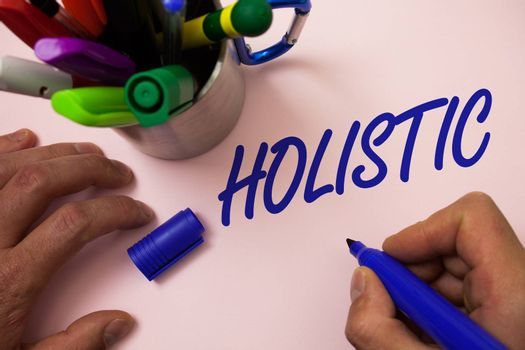 Handwriting text writing Holistic. Concept meaning Belief the parts of something are interconnected Related to holism Man working inspiration holding marker notebook ideas white background