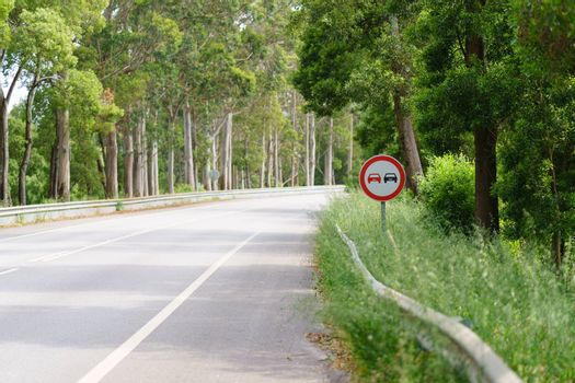 "Asphalt road through the forest in Northern Portugal. ""Prohibition of overtaking"" sign"