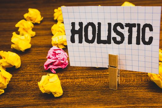 Conceptual hand writing showing Holistic. Business photo text Belief the parts of something are interconnected Related to holism Clothespin hold holding notebook paper crumpled papers ideas