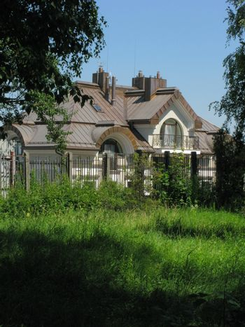 A solid house behind an iron fence with a fence with a small balcony with a growing green grass near the fence.