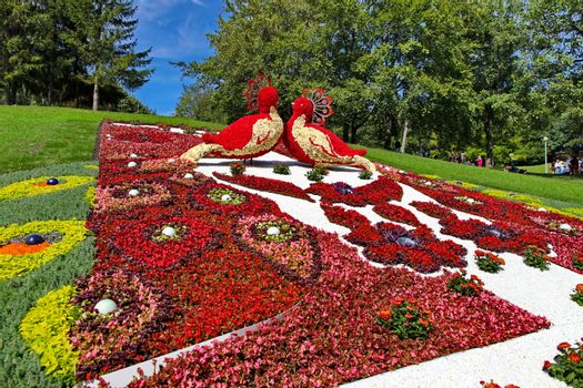 A flower bed of extraordinary beauty with statues of flowers dep