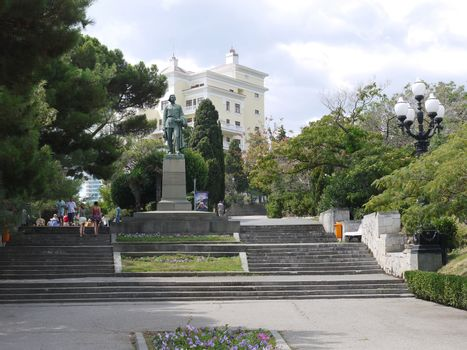 monument to Maxim Gorky at the top of the stairs against the background of trees and a tall white building