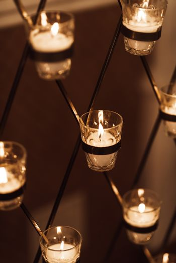 Candles burn in glasses on the wedding arch