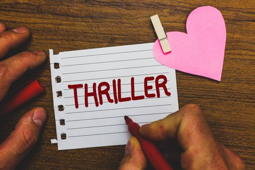 Writing note showing Thriller. Business photo showcasing Chilling frightful moments in life film and movie category Small pitch paper clip paperclip love wood black shadow creative ideas