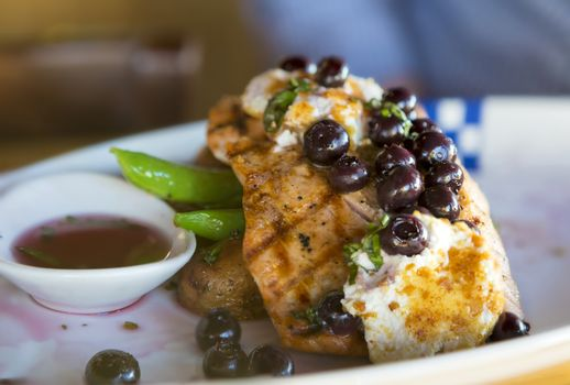 Grilled Wild Alaskan Salmon with blueberries goat cheese over potatoes green beans dinner plate closeup