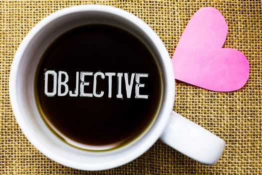 Text sign showing Objective. Conceptual photo Goal planned to be achieved Desired target Company mission Tea time coffee cup office typing work jute rough background love heart