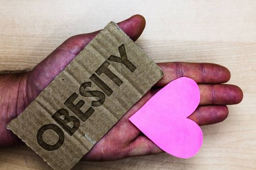 Conceptual hand writing showing Obesity. Business photo text Medical condition Excess of body fat accumulated Health problem Packing card inscribed text love heart hand recycle make useful