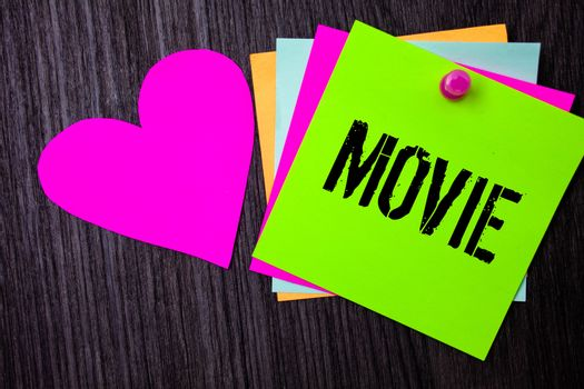 Conceptual hand writing showing Movie. Business photo text Cinema or television film Motion picture Video displayed on screen Pinned multi colour cards heart polish dark lining background